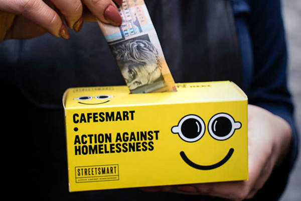 $50 being put in a cafesmart moneybox
