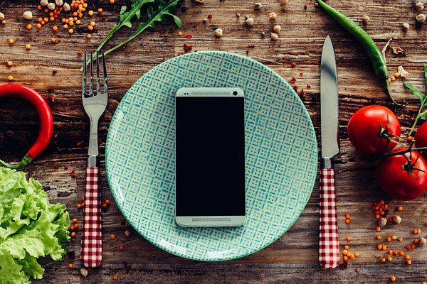 mobile phone on a plate with knife and fork
