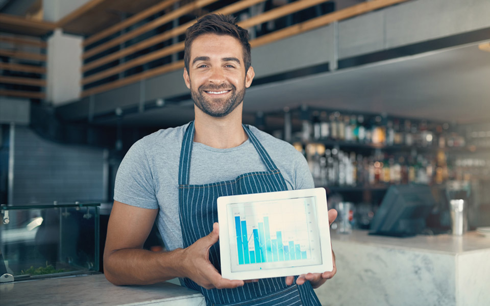 restaurant manager holding tablet with pos system reports
